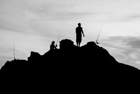 Black and white two man fishing on sea shore Reklamní fotografie