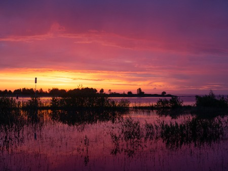 Bright red-violet dawn on the shore of the lake. Reflection in water. Stock Photo