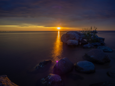 Impressive dawn on the lake. Stones in the water. Stock Photo