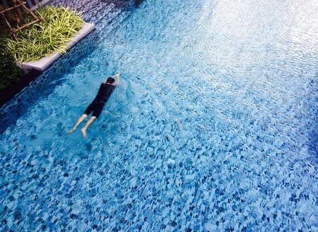 man: Man swimming in a pool