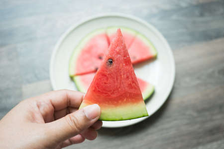 woman hands is holding the piece of watermelon