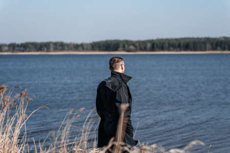 A man in a black coat stands in the middle of dry grass on the riverbank. Reklamní fotografie