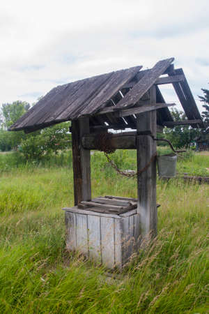 Ancient wooden well with a chain and a bucket Standard-Bild
