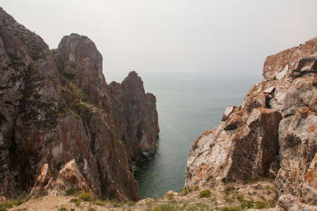 A high rocky coastline a cliff in the sea a lake and fog over the water Banco de Imagens