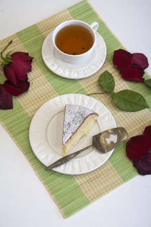 Morning biscuit cake with cup of tea on white