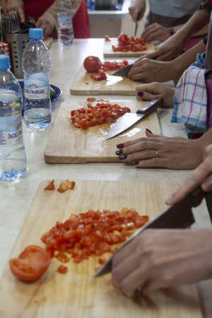 Chef giving cooking classes in kitchen proper slicing tomatoes
