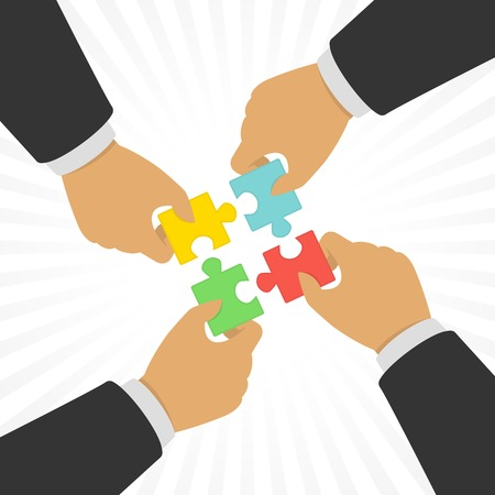 Hands putting puzzle pieces together.