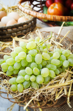 willow fruit basket: Grapes and eggs on a straw bedding in the wicker plates with wooden and sackcloth background
