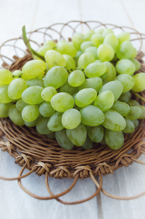 willow fruit basket: Bunch of grapes in a wicker plate on a white wooden background