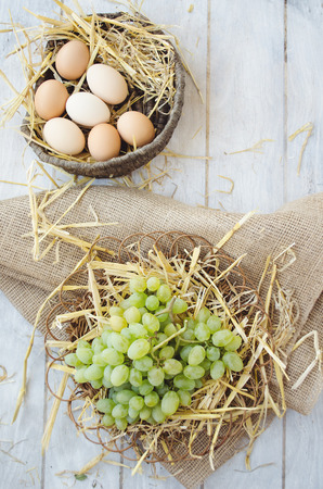 willow fruit basket: Organic grapes and eggs on a straw bedding in the wicker plates with wooden and sackcloth background Stock Photo