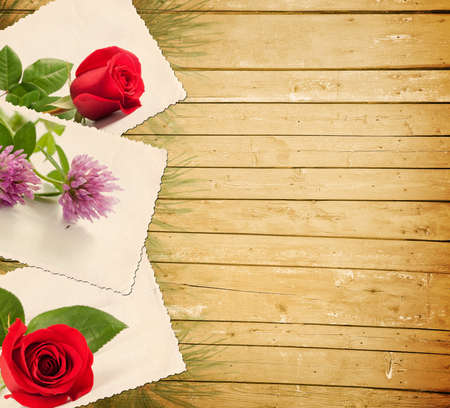 Old photo with flowers on a wooden background photo