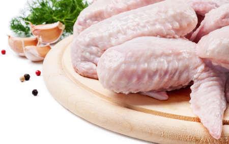 alitas de pollo: Alas de pollo crudo en un tablero de madera con el eneldo y el ajo Foto de archivo