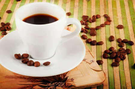 Vintage background with coffee cup and coffee beans  on green bamboo stand photo
