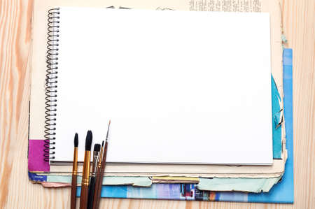 Blank notebook, brushes and old paper sheet on a wooden surface photo