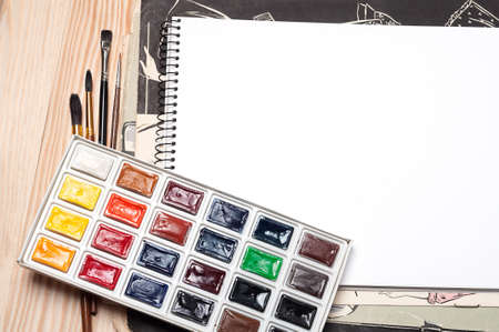 Blank notebook, brushes and watercolor on a wooden surface photo