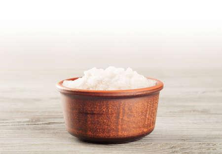 sal: Sal de baño aromático en una taza de arcilla en una superficie de madera