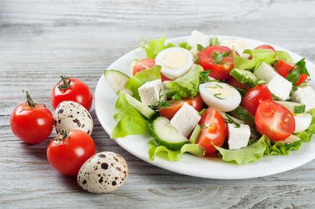 Ensalada fresca con huevos de codorniz, tomate cherry, pepino y lechuga en un fondo de madera
