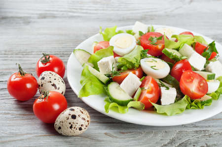 codorniz: Fresh salad with quail eggs, cherry tomato, cucumber and lettuce on a wooden background