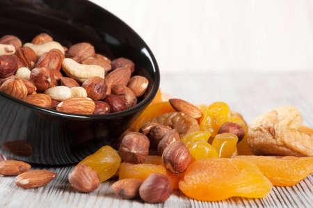 frutas deshidratadas: Las frutas secas y frutos secos sobre un fondo de madera. frutas confitadas, limón, albaricoque, higos y frutos secos en un plato negro.