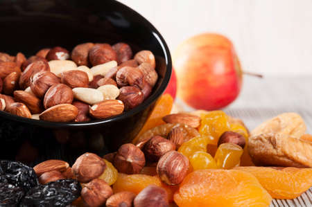 Dried fruits, lemon, apricot, fig and nuts in black plate on a wooden background.