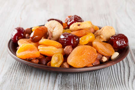 frutas deshidratadas: Dried fruits on a wooden background. Dates, lemon, apricots, figs and nuts in a clay plate.