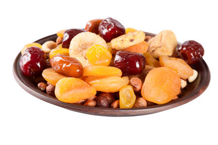 dried: Dried fruits isolated on a white background. Dates, lemon, apricots, figs and nuts in a clay plate.