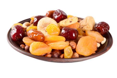 frutas deshidratadas: frutos secos aislados sobre un fondo blanco. Fechas, limón, albaricoques, higos y frutos secos en un plato de barro. Foto de archivo