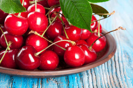 plate: Red sweet cherry and green leaves in a clay dish on a blue wooden background Stock Photo