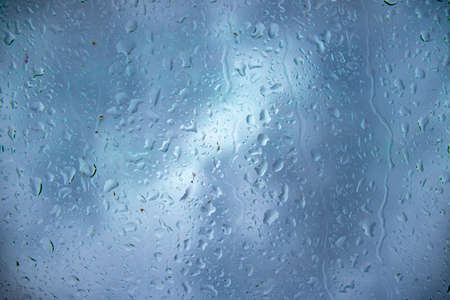 Raindrops on the glass and water runs down the glass, photography and background. Rain, water, nature and rainy weather, photo