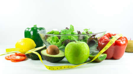Healthy salad diet food props decoration kiwi, tomatoes, apple, avocado, Red chilli, Green pepper , lemon and measuring tape ,top view. Reklamní fotografie