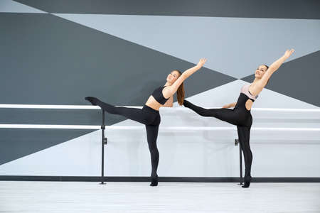 Smiling adult female instructor helping young girl in black sportswear learn choreographic move, holding handrail. Two synchronized women practicing stretching in hall. Gymnastics concept.