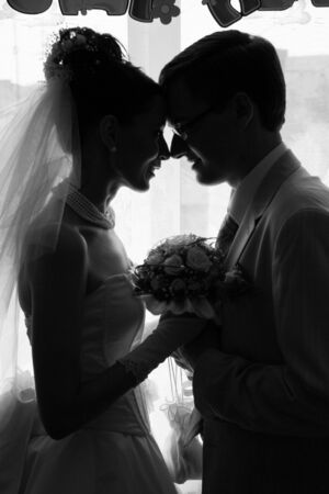 beside: Married. Newlywedses stand beside window Stock Photo