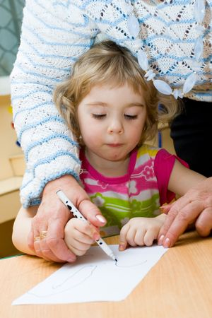 upbringing: The Small artist. Girl sits at the table and draws.