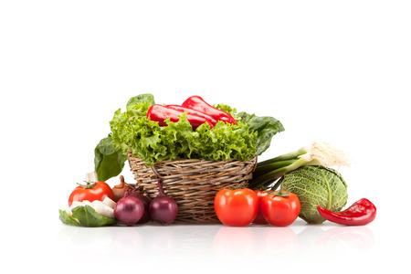 かごいっぱいに白い背景の熟した野菜の