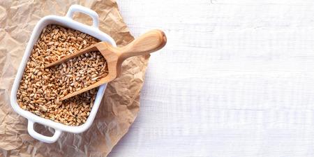 白い木製の背景の小麦種子の完全木製スコップ