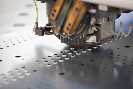 Rotation Punching & Nibbling Machine in action. Metal perforating industrial machine. Stock Photo