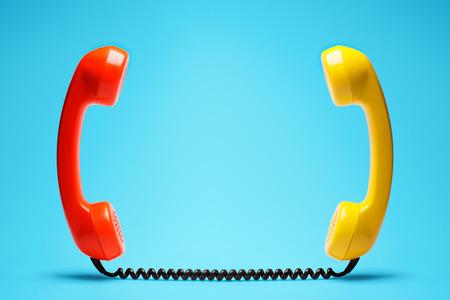 Orange and yellow telephone on blue background. Stock Photo