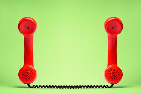 緑の背景にレトロなスタイルの2つの赤い電話。