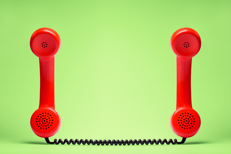Two red telephone in retro style on green background.