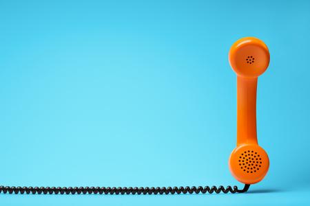 Teléfono en estilo retro en fondo azul.