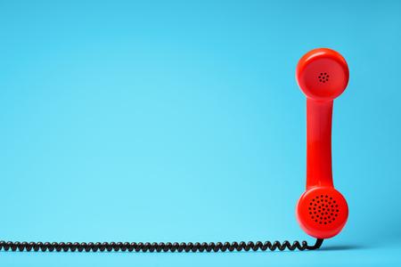 青い背景にレトロなスタイルの赤い電話。