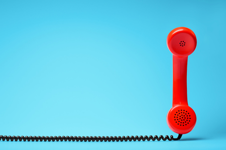 Red telephone in retro style on blue background. Stock Photo