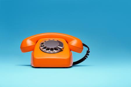 Telefoon in retro stijl op blauwe achtergrond.