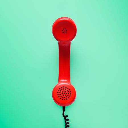 緑の背景にレトロなスタイルの赤い電話。