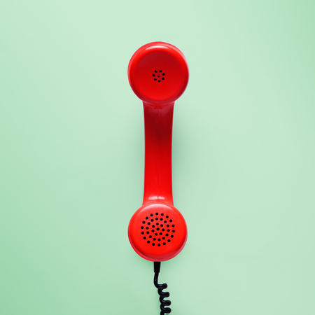Red telephone in retro style on green background.