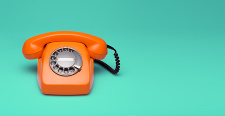 Old orange telephone rings with handset off Stock Photo