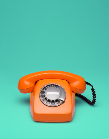 Old orange telephone rings with handset off 免版税图像