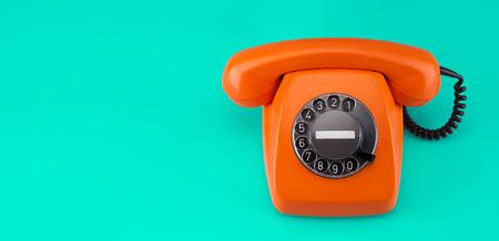Old orange telephone rings with handset off 写真素材