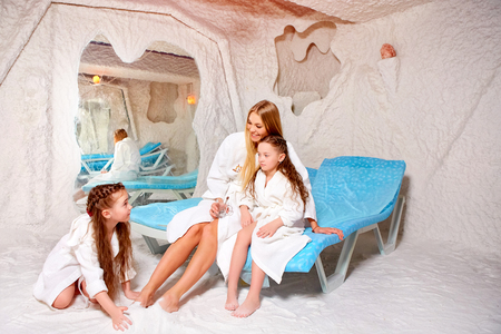 Mother with two children in salt room. Halotherapy for treatment of respiratory diseases.