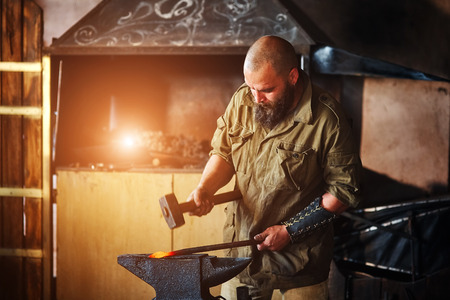 Blacksmith working in the forge. Manufacture of parts  from molten metal, using the hammer and anvil. Stock Photo